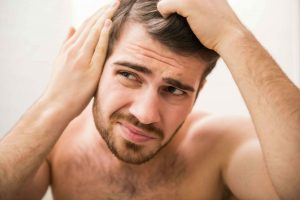 Man looking at potential bald spot
